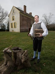 Chris Merrill, a historic site interpreter, with firewood in hand at the John Dickinson Plantation in Dover.