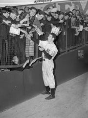 Back in his Yankee uniform after a long holdout, Joe DiMaggio is shown in this April 23, 1938 photo at Yankees Stadium in New York as he obliged autograph-seeking youngsters in the bleachers. DiMaggio, the elegant Yankee Clipper whose 56-game hitting streak endures as one of the most remarkable records in baseball or any sport, died Monday, March 8, 1999 at his home in Hollywood, Fla. He was 84.