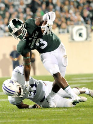 Michigan State sophomore running back LJ Scott breaks a tackle fighting for yardage against Furman Friday night. Scott rushed 20 times for 105 yards and  touchdown. No other running back carried more than five times.