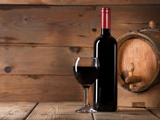 Wine bottle with glass and wooden barrel on wooden background