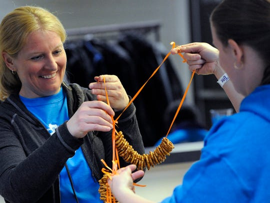 FILE - Janice Ericson, left, and Melissa Jacquart, right, untangle pretzel necklaces for customers during the 19th annual Jaycees Beer Lovers Brewfest in 2015.