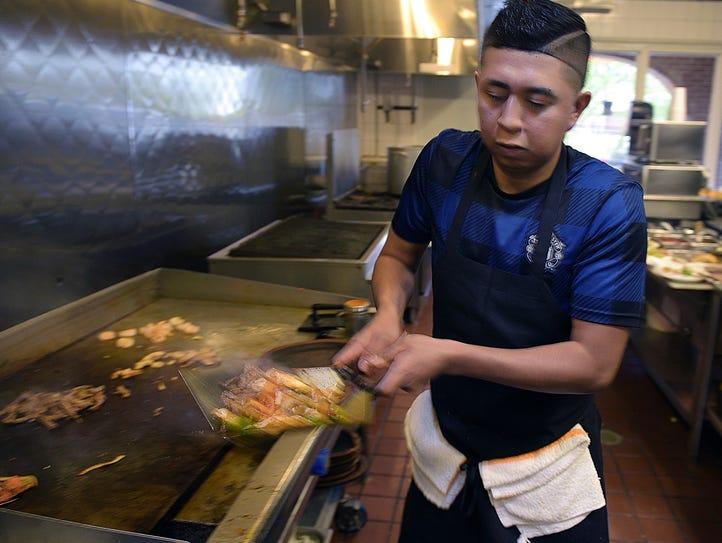 La Hacienda cook Roberto Gustamonte makes fajitas during