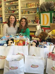 Toy Market owner Kelly Donio of Hammonton with Miss New Jersey Lindsey Giannini surrounded by toys donated by Toy Market for hospitalized children.