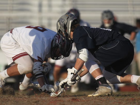 Chiles' Riley Myers tries to win a face-off against
