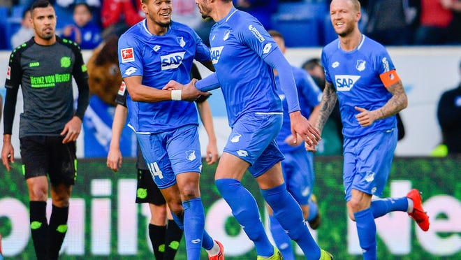 Hoffenheim's Ishak Belfodil, center right, celebrates his side second goal with Joelinton Cassio Apolinario de Lira, center left, during the German Bundesliga soccer match between TSG 1899 Hoffenheim  and Hannover 96 in  Sinsheim, Germany, Saturday, Feb, 16, 2019. (Uwe Anspach/dpa via AP)