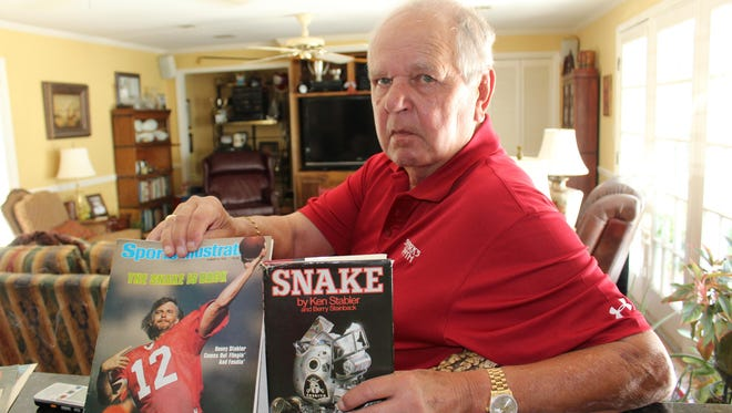 Selma lawyer Henry Pitts who was Ken Stabler's agent and close friend, holds a copy of Sports Illustrated with Stabler on the cover and a book about the quarterback's career.