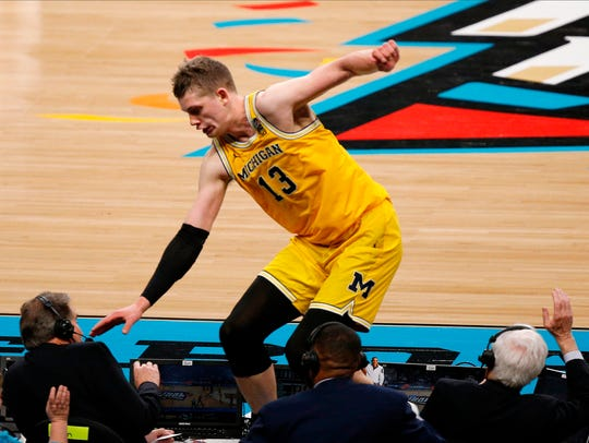 Michigan's Moritz Wagner jumps over the broadcast table