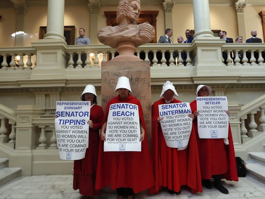Women hold signs to protest HB 481 on April 2 at the state Capitol in Atlanta. HB 481, which would ban most abortions after a fetal heart beat is detected, has past both the House and the Senate and awaits a signature from Gov. Brian Kemp.