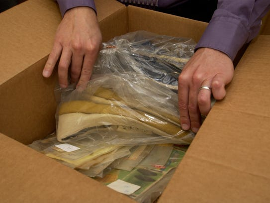 A detective thumbs through a box of evidence while