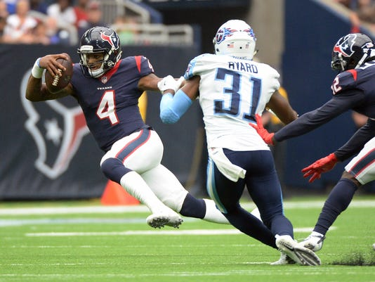 Houston Texans quarterback Deshaun Watson (4) runs around Tennessee Titans free safety Kevin Byard (31) during the second half of an NFL football game, Sunday, Oct. 1, 2017, in Houston. (AP Photo/George Bridges)