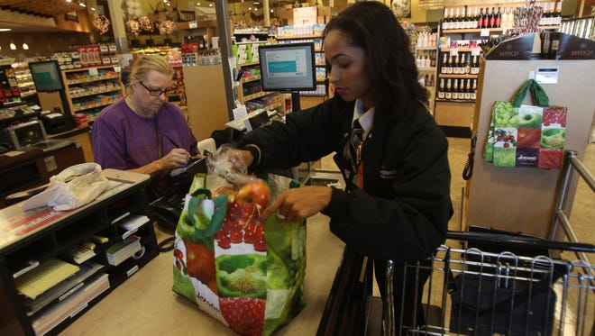 Cashier Traneace Grovy fills a customer's reusable bag Jan. 2, 2014, at Jensen's grocery in Palm Springs, Calif.