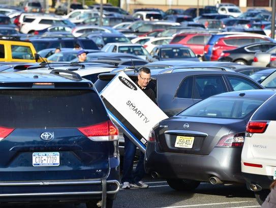 A shopper makes his way through the parking lot with