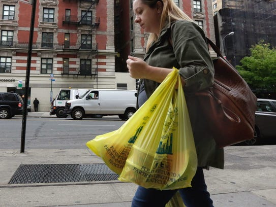 A woman carries her purchase in plastic bags from a