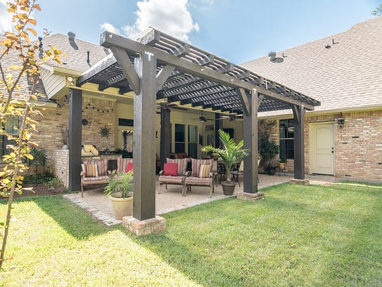 It has an expansive covered pergola with outside grill