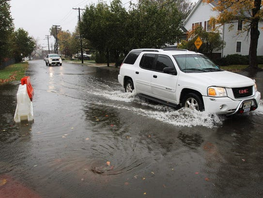 A motorist drives through flood waters at the corner