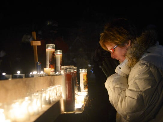 Newtown resident Pam Mickewich pray at a makeshift