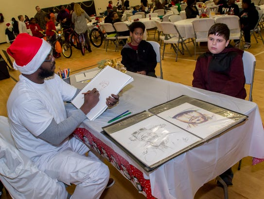 Carlos Lawrence, 11, right, poses while Carter J. draws