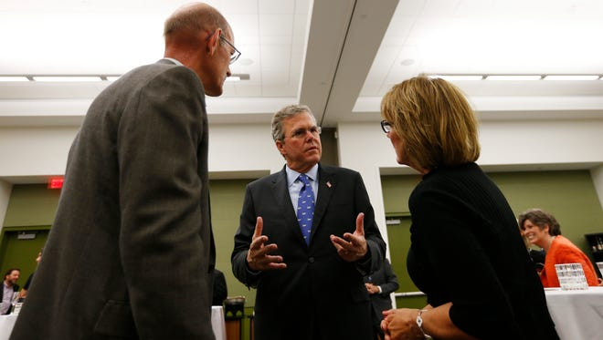 Former Florida Gov. Jeb Bush talks with Doug and Sharon Ommen of Ankeny on Saturday following the Republican Party of Iowa's Lincoln Dinner in Des Moines.