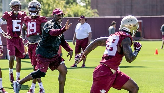 FSU defensive coordinator Harlon Barnett works a drill with players as Mickey Andrews, in the background, observes.