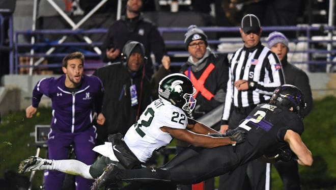 Northwestern Wildcats wide receiver Flynn Nagel (2) avoids a tackle by Michigan State Spartans cornerback Josiah Scott (22) to score a touchdown during triple overtime at Ryan Field.