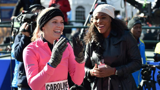Tennis player Caroline Wozniacki reacts after crossing the finish line as Serena Williams watches at the New York City Marathon in New York.