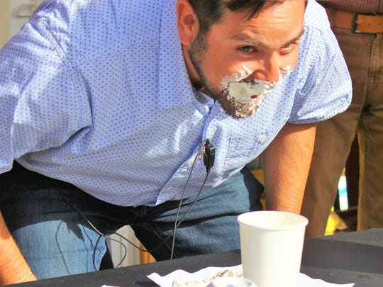 Steve Gomez takes it in the face for the opening of the drive-through and online ordering at his Cornerstone Bakery.
