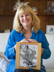 Elizabeth McBride was 10 years old when her father's plane was shot down in Vietnam. Here she holds one of her favorite photos of him.
