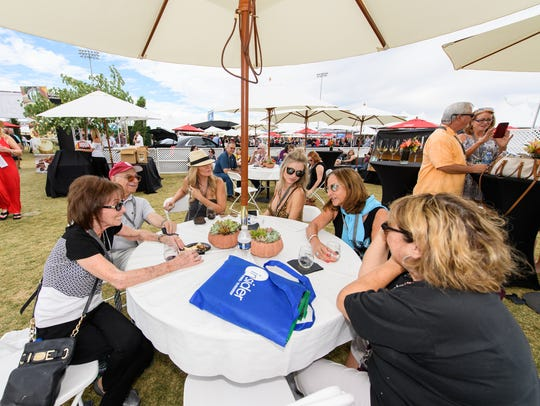 Crowds relax at the AJ's Fine Foods VIP tent at the