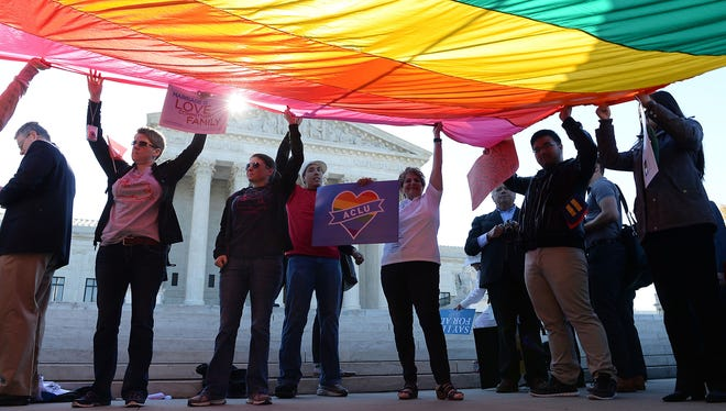 Gay marriage advocates hold a rainbow flag in front of the Supreme Court as arguments began in a collection of same-sex marriage cases in 2015.