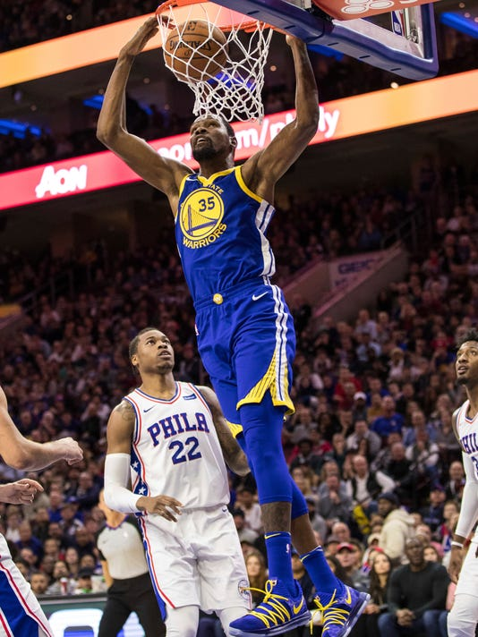 Golden State Warriors' Kevin Durant (35) dunks as Philadelphia 76ers' Richaun Holmes, left, looks on during the first half of an NBA basketball game Saturday, Nov. 18, 2017, in Philadelphia. (AP Photo/Chris Szagola)