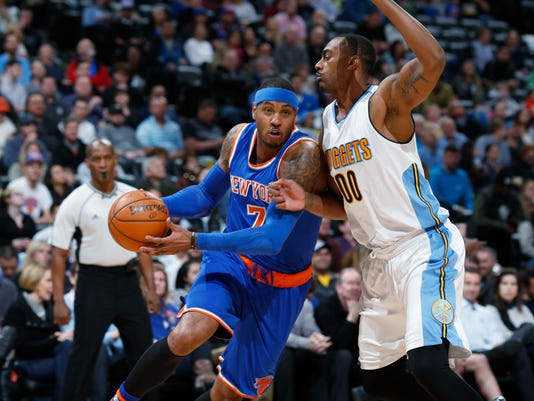 New York Knicks forward Carmelo Anthony, left, drives for a basket pastor Denver Nuggets forward Darrell Arthur in the first half of an NBA basketball game, Tuesday, March 8, 2016, in Denver. (AP Photo/David Zalubowski)