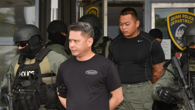 Department of Corrections Lt. Jeffrey Limo, left, and Officer Franklin Rosalin, right, are escorted out of the Guam Police Department Hagatna precinct after being arrested on Thursday, Aug. 24, 2017. The two were among five DOC officers and three others arrested after a raid at the Mangilao prison and two homes.