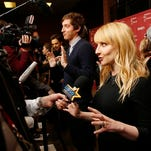 "Writer and actress Melissa Rauch, right, and actor Thomas Middleditch, rear center, are interviewed at the premiere of ""The Bronze"" during the 2015 Sundance Film Festival on Thursday, Jan. 22, 2015, in Park City, Utah. (Photo by Danny Moloshok/Invision/AP)"