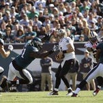 New Orleans Saints' Drew Brees is tackled by Philadelphia Eagles' Fletcher Cox during the first half of Sunday's game.