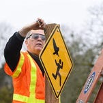 This Feb. 12 file photo shows John Kleeman, parks operations supervisor for Salem, Ore., installing a sign at Bush's Pasture Park warning visitors of recent owl attacks. The year is ending the way it began in Salem, with an aggressive owl going after people. At least two attacks have been reported more than a mile north of a park where joggers were attacked in January, said Julie Curtis, spokeswoman for the Department of State Lands.