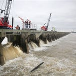 "Cranes atop the weir separating the Mississippi River from the Bonnet Carre Spillway in Norco, La., began pulling long creosoted timber ""needles"" from the first of 350 bays at about 10:45 a.m. Sunday, Jan. 10, 2016,part of a plan to reduce the river's flow as it moves past New Orleans by directing part of its water into Lake Pontchartrain. (Kathleen Flynn/NOLA.com The Times-Picayune via AP)"