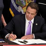 New York Gov. Andrew Cuomo signs a law that will gradually raise New York's minimum wage to $15, at the Javits Convention Center, in New York, Monday, April 4, 2016. (