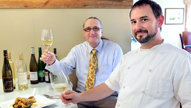 """Sommelier Craig Richardson, left, and chef Terry White enjoy a glass of Riesling wine.  Photos by Glenn Beil/Democrat Sommelier Craig Richardson, left, and chef Terry White enjoy a glass of Reisling wine. Reisling, a white wine that many assume is too sweet to be refreshing or food friendly, is all over the menu at Sage as it joins a nationwide campaign """"Summer of Reisling."""""""