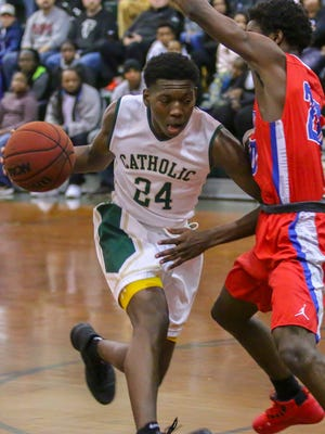 Catholic's DJ McKenzie (24) races around Pine Forest's Devon Witherspoon (20) in the championship game of the 6th annual Crusader Classic at Catholic High School on Friday, December 29, 2017. Catholic won 47-40.