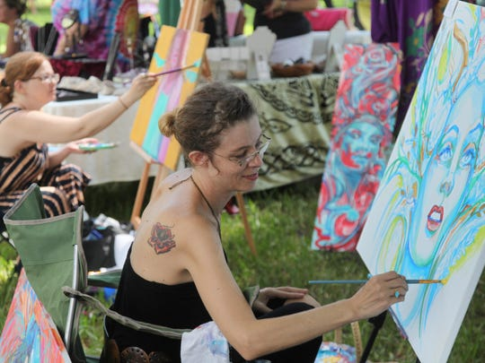 Artists Dharma Lefevre, front, and Lesley Morrow paint while attending the 8th Annual Peace Day in the Park at Jaycee Park in Cape Coral on Sunday.