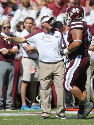 Mississippi State coach Dan Mullen talks to Nick James after he received a personal foul penalty against Auburn on Saturday.