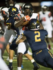 Lely running back Wendy Yonard is hit by Andre Eaton of Naples during the game at Naples High Friday night, October 6, 2017.