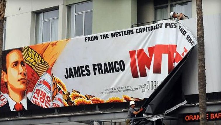 """Workers remove a poster for """"The Interview"""" from a"""
