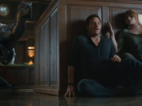 """Coming to a home near you: dinosaurs. Owen (Chris Pratt) and Claire (Bryce Dallas Howard) hide from an Indoraptor in """"Jurassic World: Fallen Kingdom."""""""