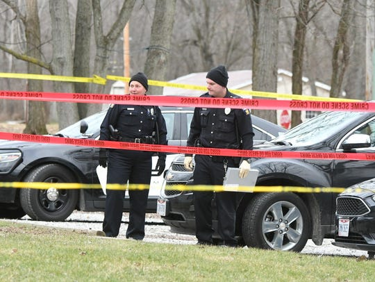 Police officers on the scene of a homicide at 1247A