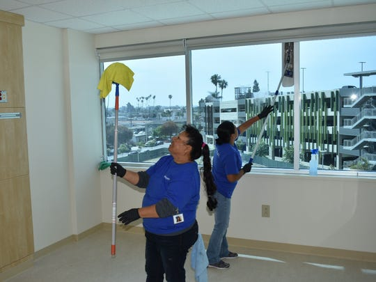 Workers clean one of the 250 patient rooms in the new Community Memorial Hospital tower in Ventura.