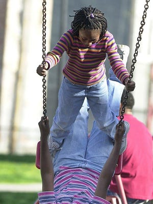Ziegler Park has drawn families and children for years, including these two girls in 2001. Soon, it will be redeveloped.