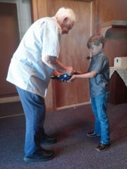 Bill Master, of Elmdale Baptist Church, shows Will Hardin how to properly fold the American flag.
