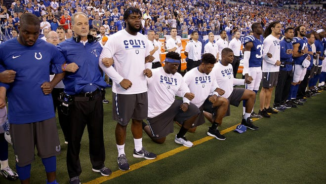 Several Indianapolis Colts players kneel as others stand with arms locked during the national anthem before the start of their game against the Cleveland Browns at Lucas Oil Stadium Sunday, Sept. 24 2017.
