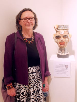 "Silver City artist Karen Lauseng poses with her piece ""Goddess of the Sea"" on Thursday during the opening of her art exhibition ""Playful Intent"" at McCray's Gallery on the Western New Mexico University campus."